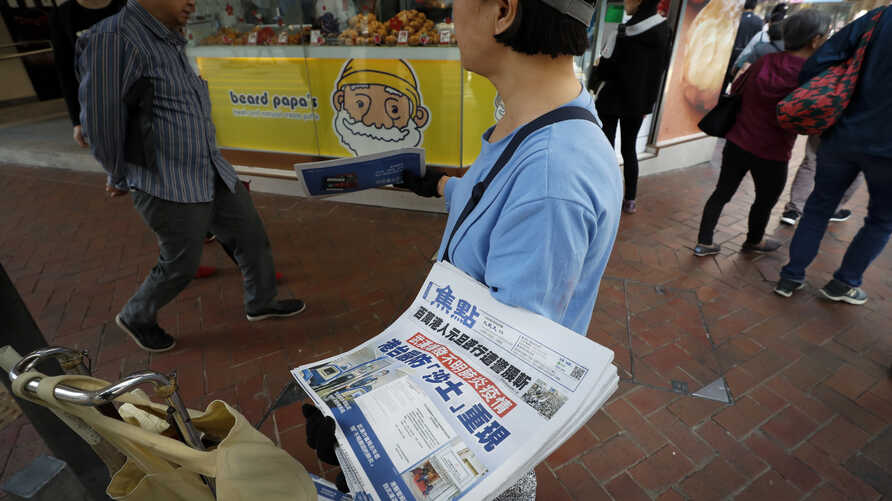 """A vendor gives out copies of newspaper with a headlines of """"Wuhan break out a new type of coronavirus, Hong Kong prevent SARS…"""