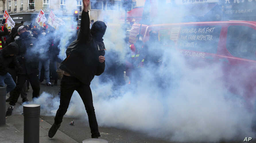Masked protestors throw debris at riot police amid tear gas smoke during a demonstration Saturday, Jan. 11, 2020 in Lille,…