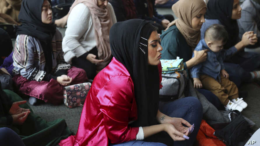 Amani Al-Khatahtbeh, center, sits at the Islamic Center of New York University during Friday prayers, Dec. 27, 2019. At 17, she and a group of friends started the blog Muslimgirl.com in response to anti-Muslim bullying they experienced after 9/11.