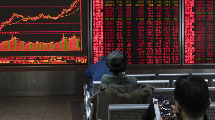 Investors monitor stock prices at a brokerage in Beijing Thursday, Jan. 16, 2020. Share prices are mixed in moderate trading in…