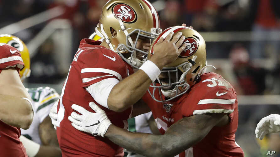 San Francisco 49ers running back Raheem Mostert, right, celebrates his touchdown with quarterback Jimmy Garoppolo during the…