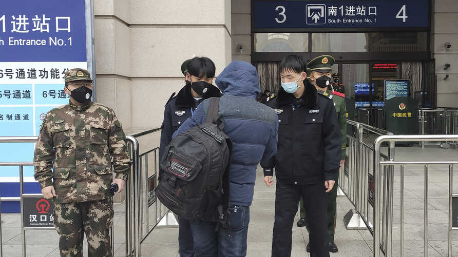 Security officers check a person at an entrance to the Hankou Railway Station in Wuhan in central China's Hubei Province, Jan. 23, 2020.