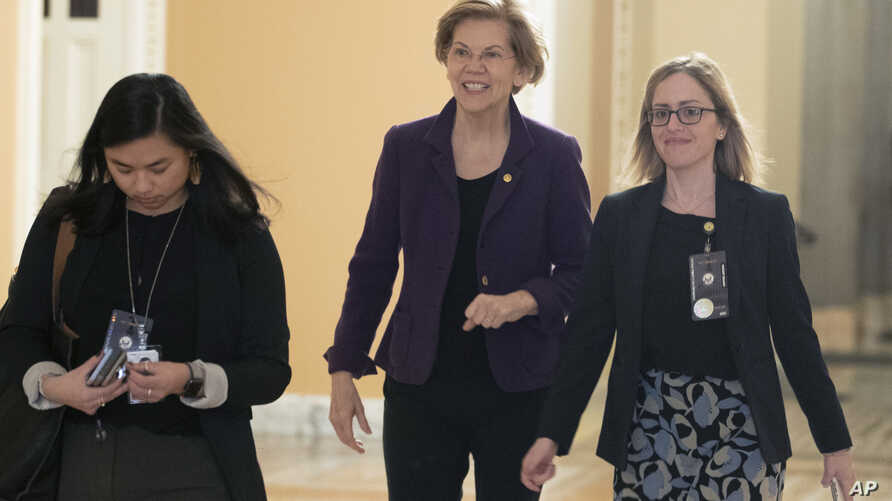 Sen. Elizabeth Warren, D-Mass., center, walks to the Senate chamber for the impeachment trial of President Donald Trump at the Capitol, Jan. 23, 2020, in Washington.