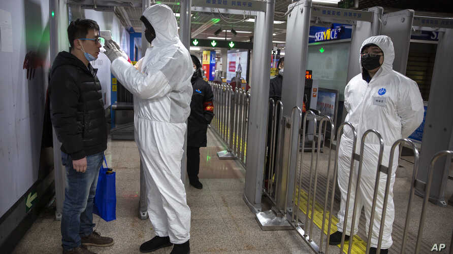 A worker wearing a hazardous materials suit takes the temperature of a passenger at the entrance to a subway station in Beijing.