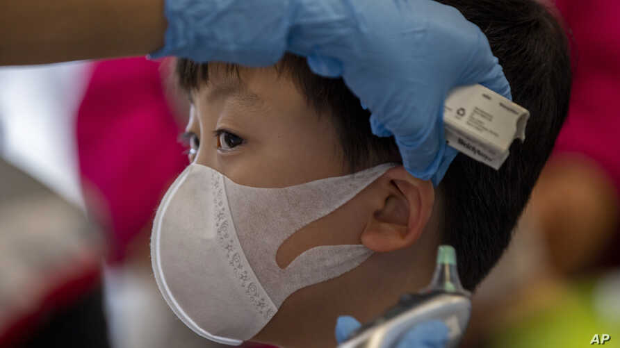 A health worker checks the temperature of tourist from Wuhan, China, as he waits for a charter flight back to Wuhan at the Suvarnabhumi airport, Bangkok, Thailand, Jan. 31, 2020.