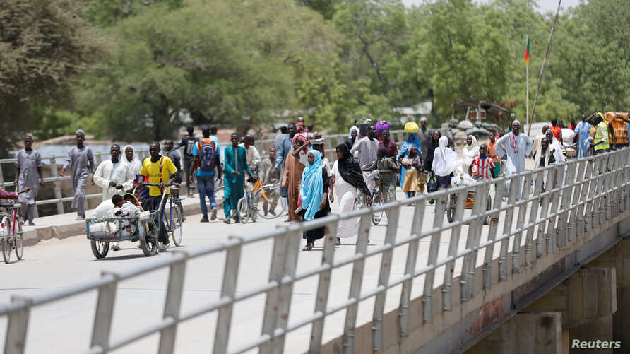 People cross a bridge linking Cameroon and Nigeria at Gamboru/Ngala in Borno, Nigeria April 27, 2017. REUTERS/Afolabi Sotunde -…