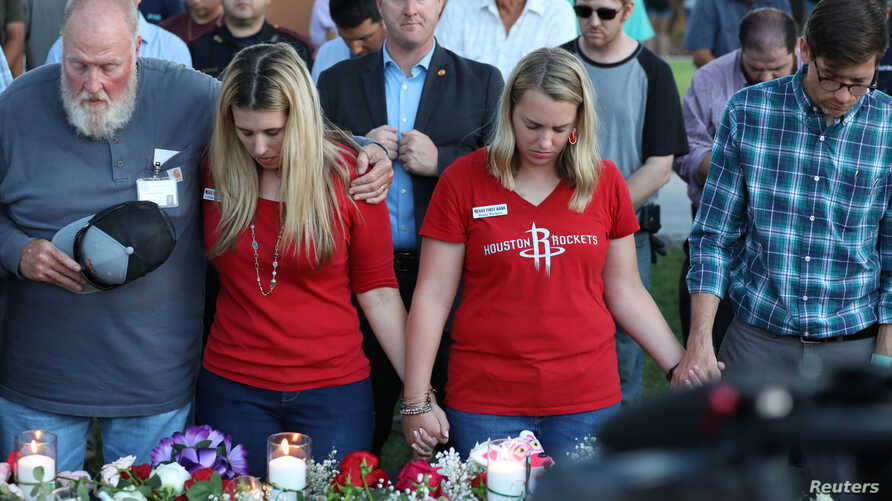 Mourners bow their heads in prayer during a vigil held  after a shooting left several people dead at Santa Fe High School
