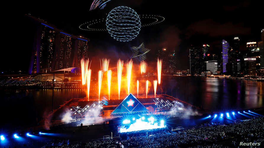 Drones perform an aerial display over Marina Bay during New Year's Eve celebrations ahead of the new year in Singapore December…