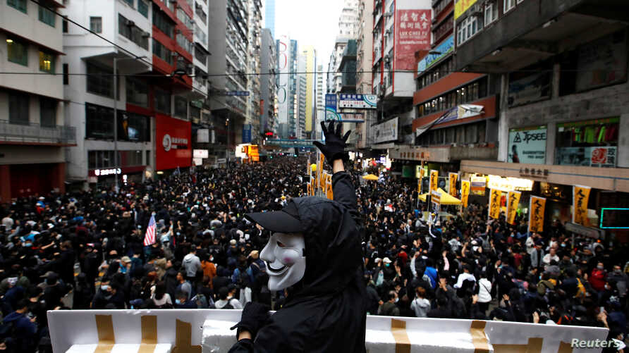 An anti-government protester wearing a Guy Fawkes mask takes part in a demonstration during New Year's Day to call for better…