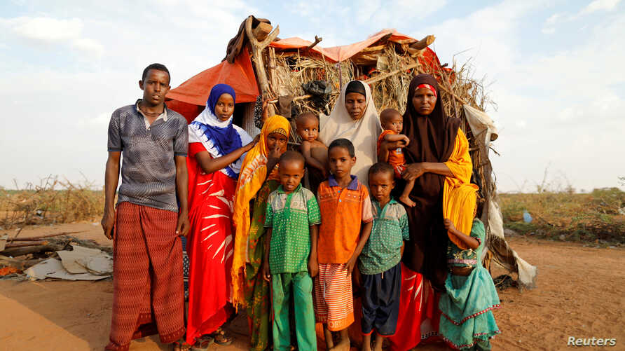 FILE PHOTO: Zeinab, 14, (2nd L) poses for photograph with her family beside their shelter at a camp for internally displaced…