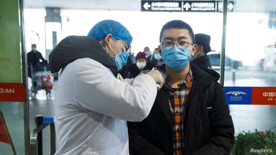 A medical official takes the body temperature of a man at the departure hall of the airport in Changsha, Hunan Province, China.