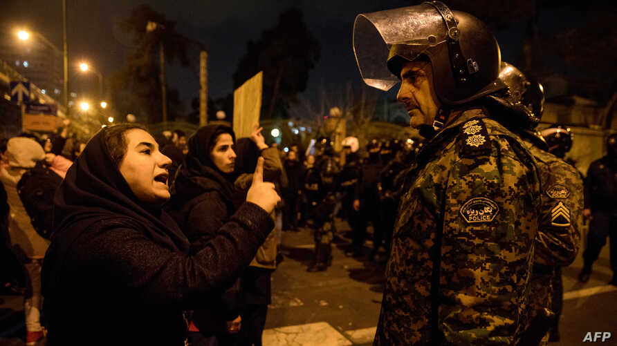 A woman attending a candlelight vigil in memory of the victims of a Ukrainian airliner downed by Iran talks to a policeman following the gathering in front of the Amirkabir University in Tehran, Iran, Jan. 11, 2020.
