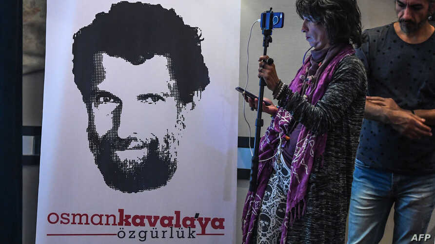 FILE - A journalist stands in front of a poster featuring jailed philanthropist Osman Kavala, during a press conference given by his lawyers, in Istanbul, Turkey, Oct. 31, 2018.