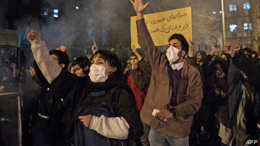 "Protesters chant slogans and hold a placard reading in Farsi ""Your mistake was unintentional, your lie was intentional,"" during an anti-govenrnment rally outside Amir Kabir University, in Tehran, Iran, Jan. 11, 2020."