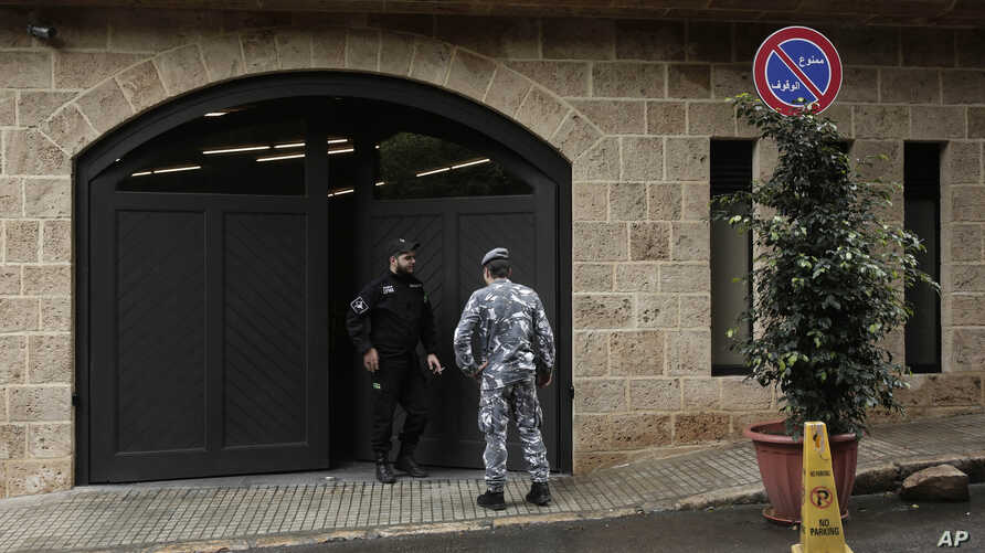 A private security guard speaks with a policeman at the residence of former Nissan chairman Carlos Ghosn, in Beirut, Lebanon, Dec. 31, 2019.