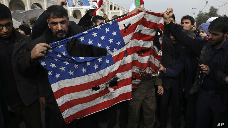 FILE - Protesters deface an American flag during an anti-U.S. rally over the U.S. airstrike in Iraq that killed Iranian Revolutionary Guard Gen. Qassem Soleimani, in Tehran, Iran, Jan. 3, 2020.