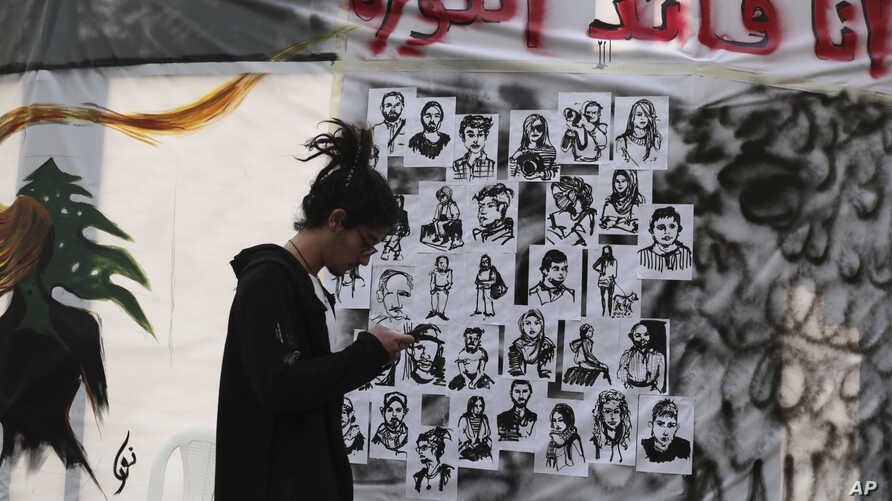 "FILE - An anti-government protester checks his mobile phone in front of a wall of graffiti in Arabic that reads, ""I am the revolution leader,"" in downtown Beirut, Lebanon, Nov. 21, 2019."
