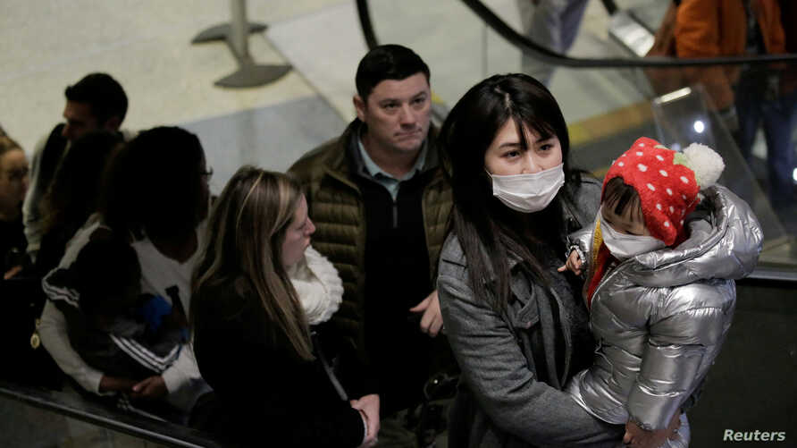 Travelers wearing masks arrive on a direct flight from China at Seattle-Tacoma International Airport in SeaTac, Washington, Jan. 23, 2020.