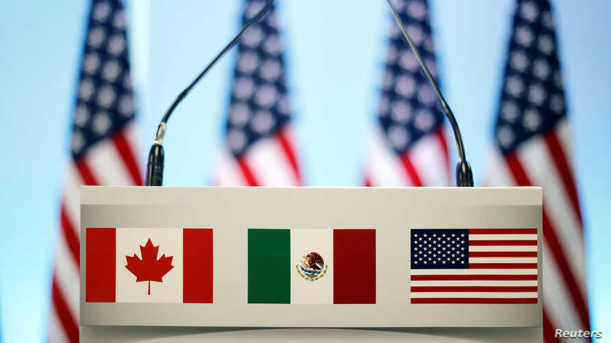FILE - The flags of Canada, Mexico and the U.S. are seen on a lectern before a joint news conference during NAFTA talks in Mexico City, Mexico, March 5, 2018.