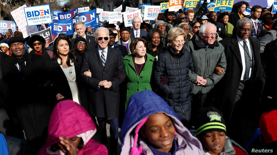 Democratic presidential rivals Tulsi Gabbard, Joe Biden, Amy Klobuchar, Elizabeth Warren and Bernie Sanders link arms during a Martin Luther King Jr. Day march, Jan. 20, 2020, in Columbia, South Carolina.