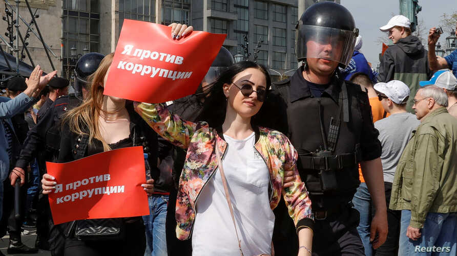 "FILE - Policemen detain demonstrators during a protest in Moscow, Russia, May 5, 2018. The posters reads ""I am against corruption."""