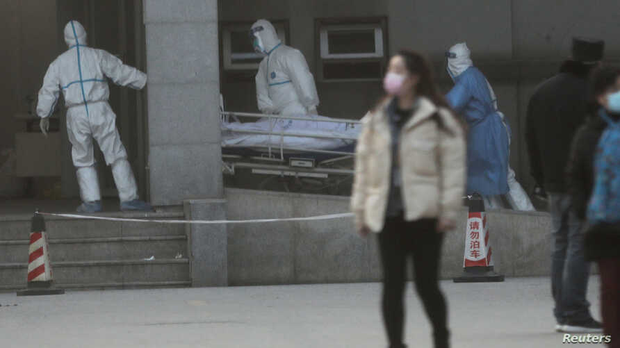 Medical staff transfer a patient at the Jinyintan hospital, where the patients with pneumonia caused by the new strain of coronavirus are being treated, in Wuhan, Hubei province, China, Jan.20, 2020.