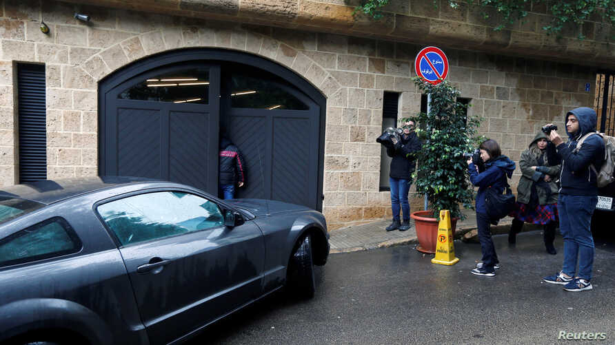 Journalists are seen near a car entering the garage of a house believed to belong to former Nissan chairman Carlos Ghosn in Beirut, Lebanon, Jan. 2, 2020.