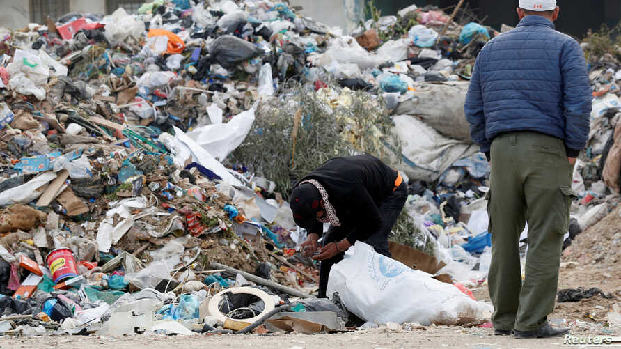 A man searches for useable items from a pile of garbage in Tunis, Tunisia, Nov. 23, 2019.