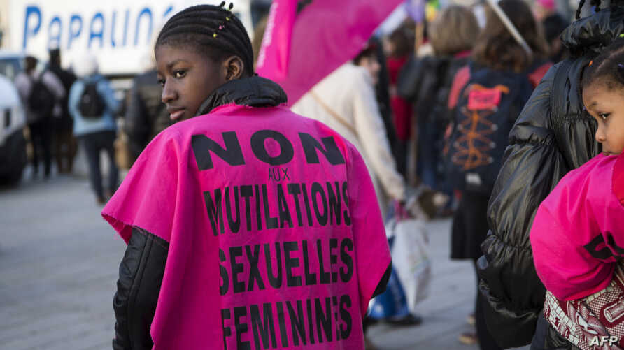 """A woman wears a jersey reading """"No to female genital mutilation"""" during a demonstration to defend women's rights on…"""