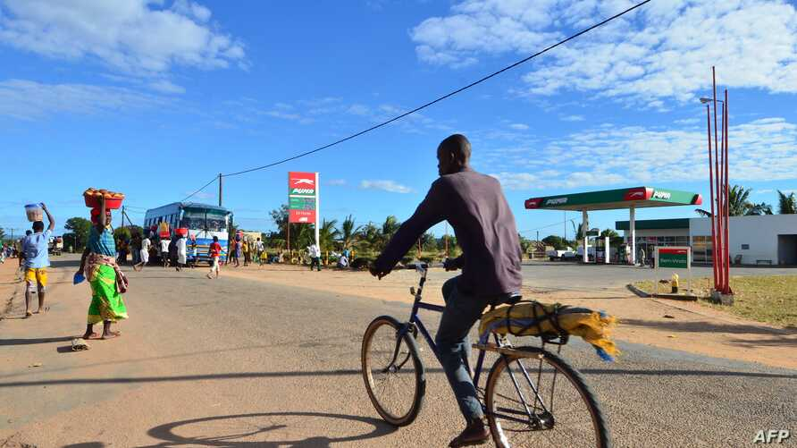 A man cycles along a street past a gas station, June 11, 2018, in Macomia, Northern Mozambique. Cabo Delgado, a northern province expected to become the center of a natural gas industry after several promising discoveries, has seen a string of assaults on security forces and civilians since October.