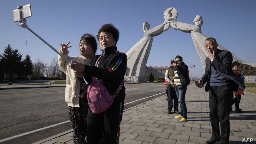 (FILES) In this file photo taken on April 15, 2019 tourists from China pose for photos before the Three Charters monument in…