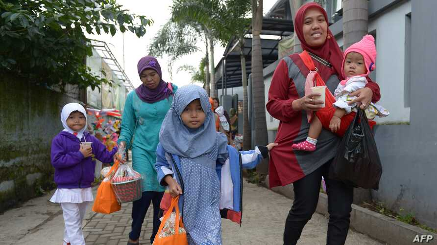 FILE - Indonesian girls with their mother leave a school-turned-clinic after the daughters were circumcised in Bandung, Feb. 10, 2013. The Indonesian government has come under fire after the U.N. General Assembly in November passed its first resolution condemning female genital mutilation.