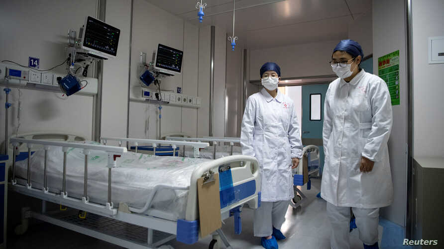 Nurses walk inside a quarantine room for coronavirus patients at finished but still unused building A2 of the Shanghai clinic