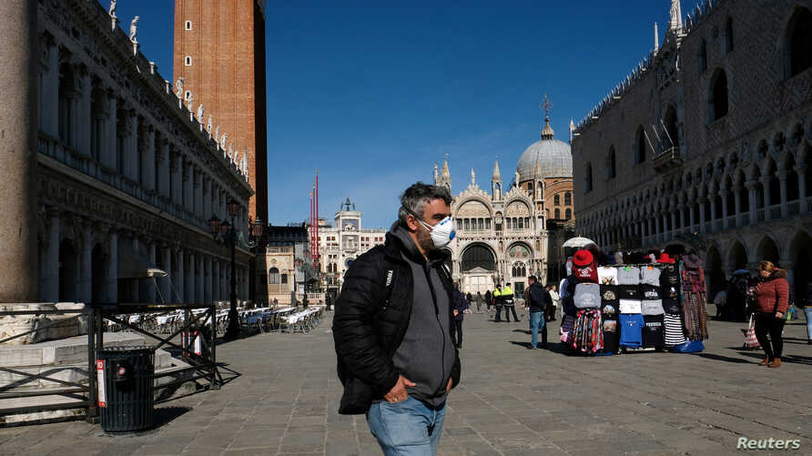 A man wearing a protective mask walks through an empty Saint Mark's Square in Venice as Italy battles a coronavirus outbreak