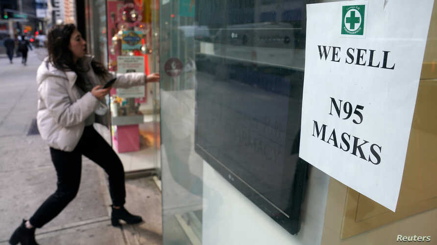 A woman walks into a pharmacy to purchase N95 face masks in advance of the potential coronavirus outbreak in Manhattan.