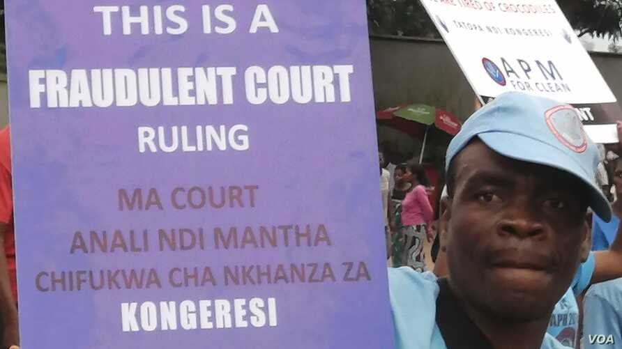 A supporter for Malawi's ruling party carries a placard which denounces the verdict by the Constitutional Court which nullifed the May presidential elections, in Blantyre, Feb. 17, 2020. (Lameck Masina/VOA)