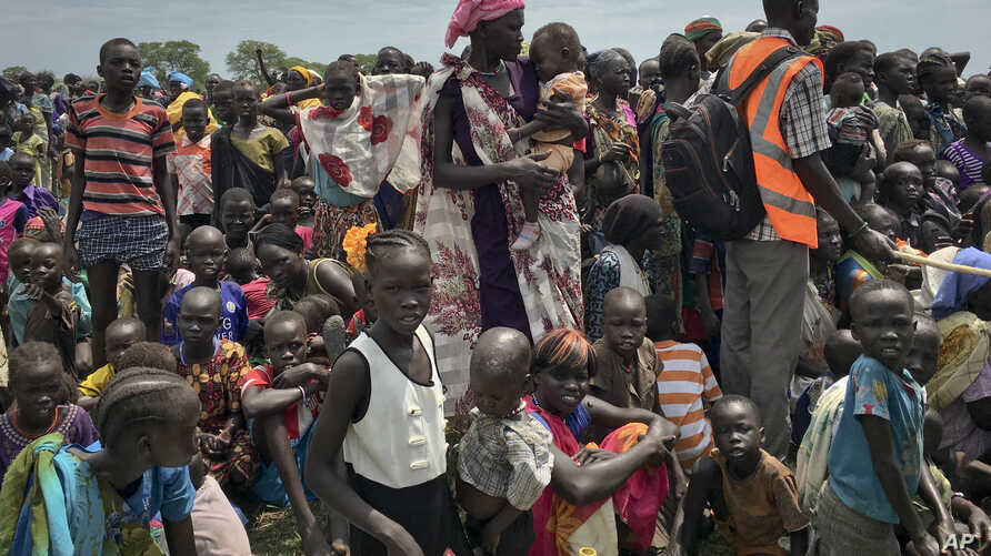 FILE - Men, women and children line up to be registered with the World Food Programme (WFP) for food distribution in Old Fangak, in Jonglei state, South Sudan, June 17, 2017.