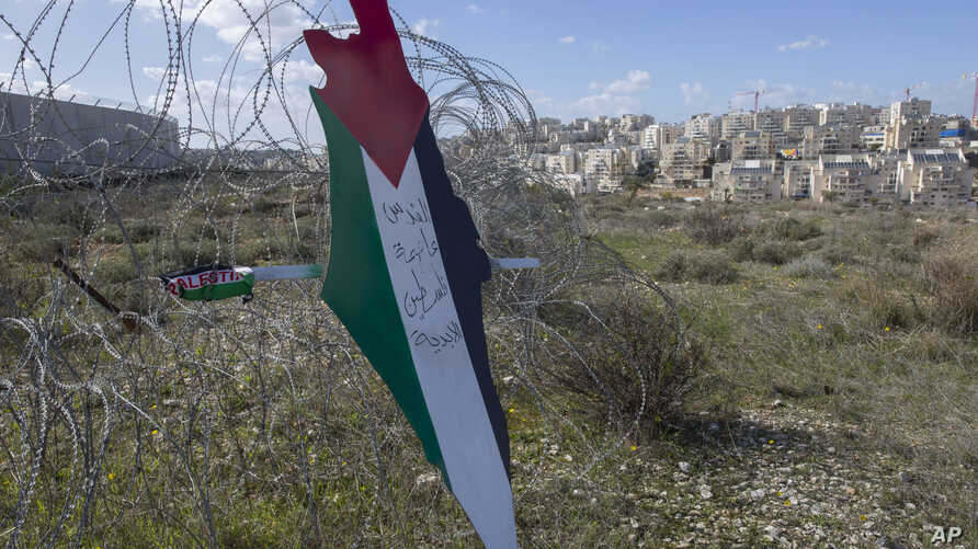 """Protesters post a placard with the colors of the Palestinian flags and Arabic that reads """"Jerusalem is the eternal capital of Palestine,"""" at a barbed wire surrounding the Israeli separation wall and an Israeli settlement near Ramallah, Jan. 31, 2020."""
