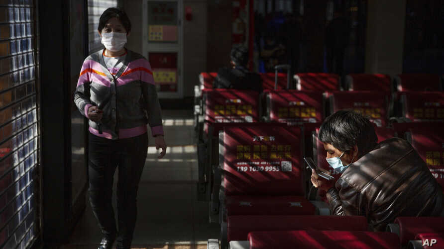 Travelers wear face masks as they wait for trains the Beijing Railway Station in Beijing, Jan. 31, 2020.