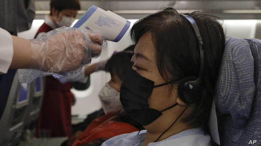 Stewardesses take temperatures of passengers as a preventive measure for the coronavirus on an Air China flight from Melbourne to Beijing before it land at Beijing Capital International Airport in China, Feb. 4, 2020.