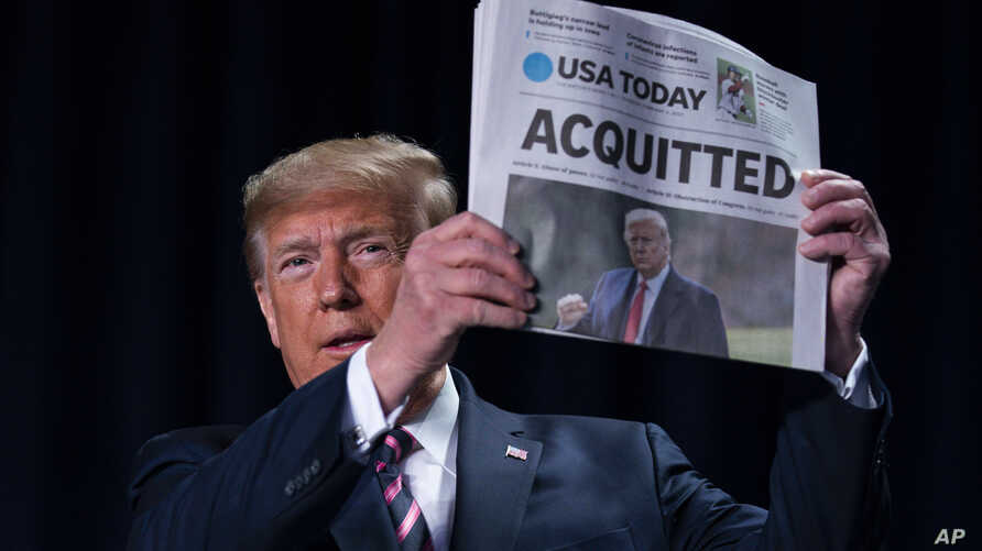 "President Donald Trump holds up a newspaper with the headline that reads ""ACQUITTED"" at the annual National Prayer Breakfast."