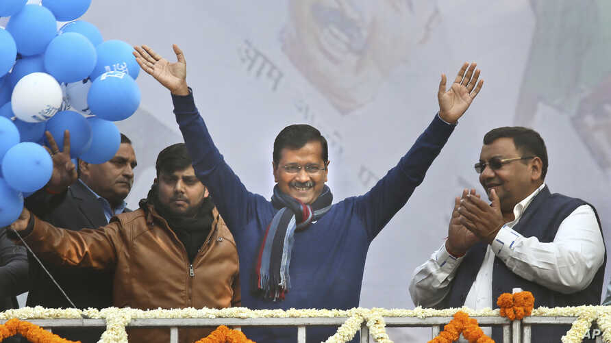 """Incumbent Delhi Chief Minister Arvind Kejriwal, center, waves at Aam Aadmi Party, or """"common man's"""" party headquarters as they celebrate the party's victory in New Delhi, India, Feb. 11, 2020."""