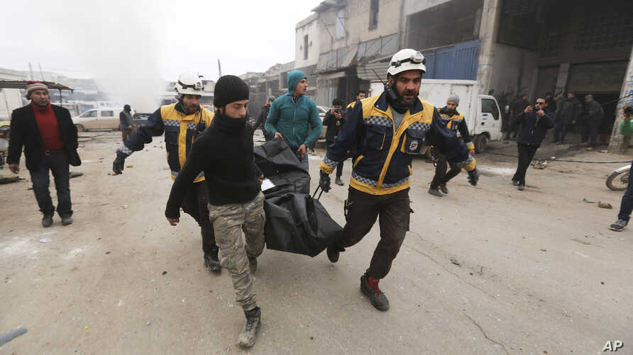Emergency services carry a body of a person killed in a government airstrike in the city of Idlib, Syria, Feb. 11, 2020.