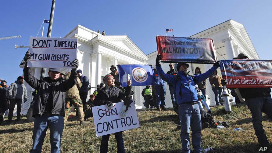 FILE - This Jan. 20, 2020 file photo shows pro gun demonstrators holding signs in front of the Virginia State Capitol in Richmond, Virginia.