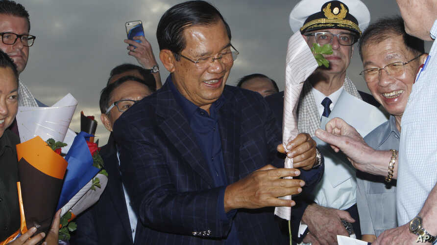 Cambodia's Prime Minister Hun Sen, center, gives a flower to a passenger who disembarked from the MS Westerdam, owned by Holland America Line, at the port of Sihanoukville, Cambodia, Feb. 14, 2020.