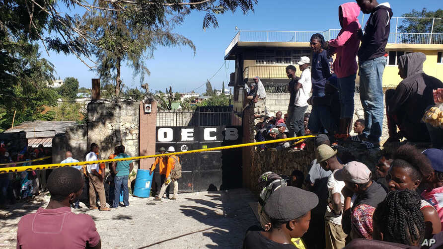 People stand outside the Orphanage of the Church of Bible Understanding where a fire broke out the previous night