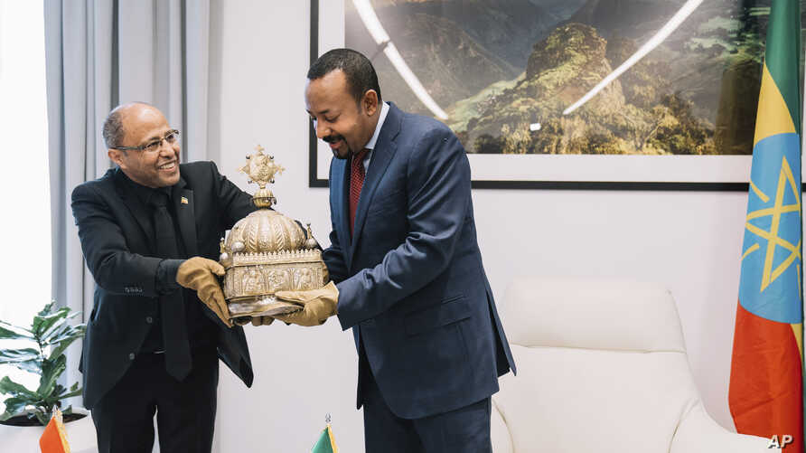 Ethiopia's Prime Minister, Abiy Ahmed, right, with gloved hands as he officially hands over a crown to the country's tourism minister, Hirut Kassaw, Feb. 20, 2020.