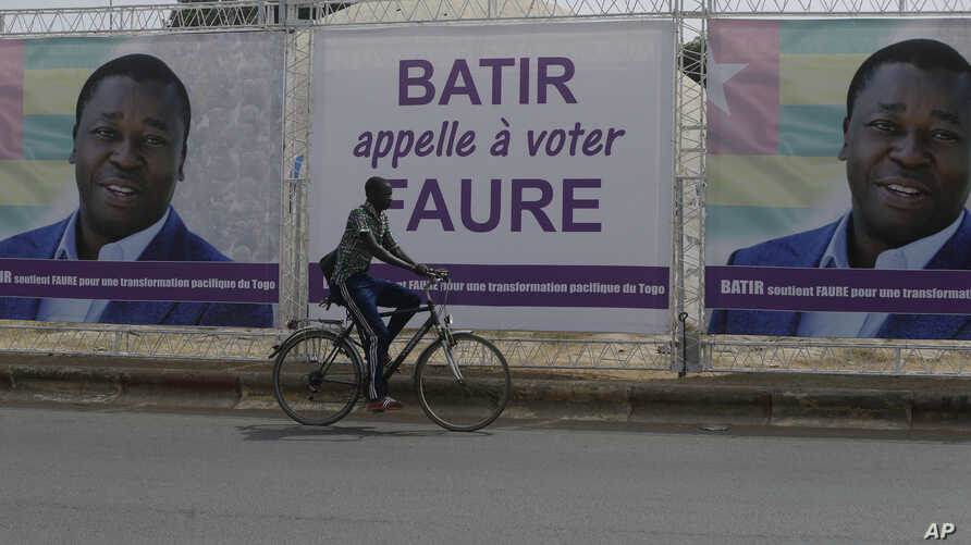 A man rides a bicycle past election posters of Togo's Incumbent President Faure Gnassingbe, Presidential Candidate of Union for the Republic, on the street in Lome, Togo, Feb. 21, 2020.