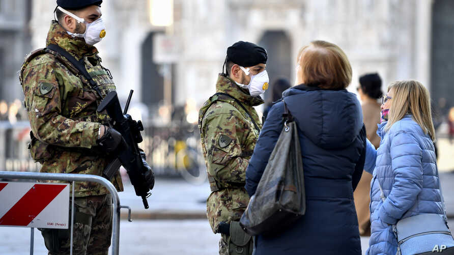 Italian soldiers wearing sanitary masks patrol Duomo square in downtown Milan, Italy, Feb. 24, 2020.