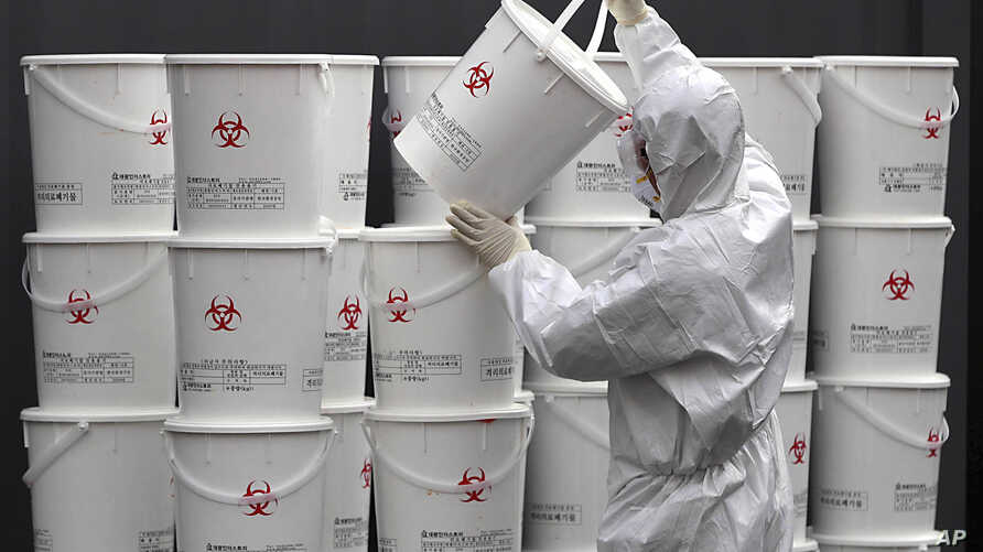 A worker in protective gear stacks plastic buckets containing medical waste from coronavirus patients at a medical center in…
